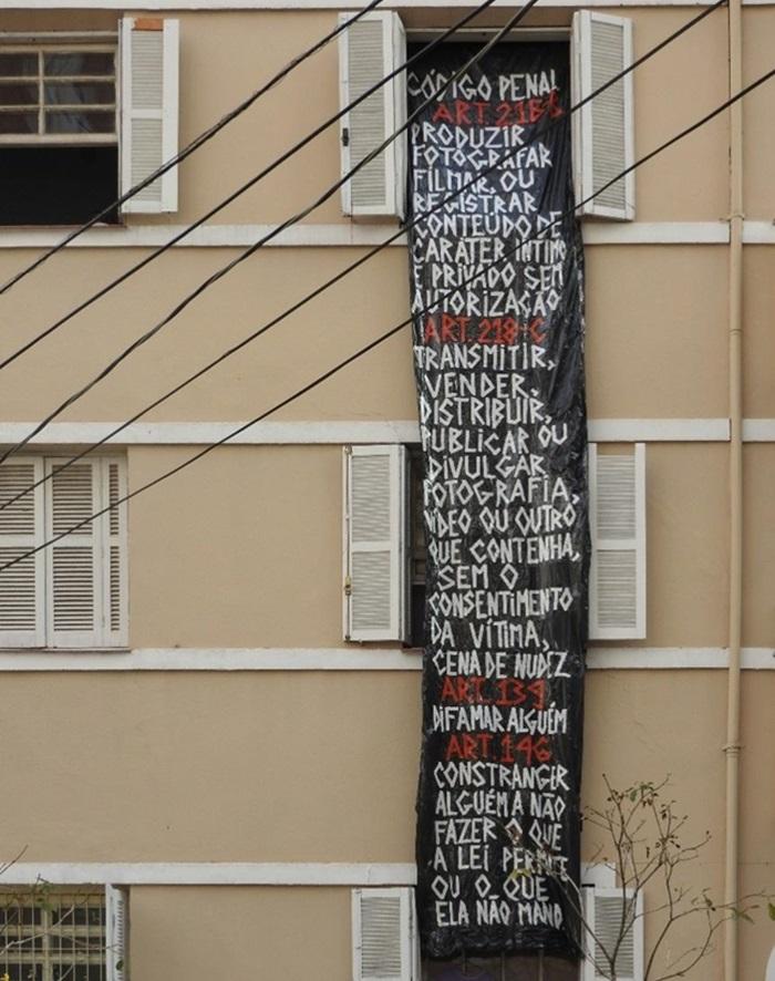 700 48 - Após ser fotografada nua dentro de casa, mulher expõe grande faixa com Código Penal na janela